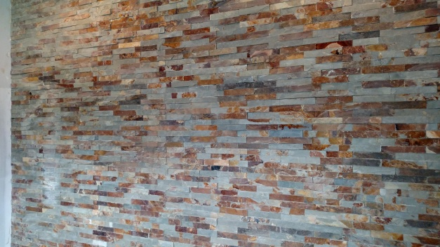 In the foyer, this is the entry way wall of tile, mimics the stone on the exterior.